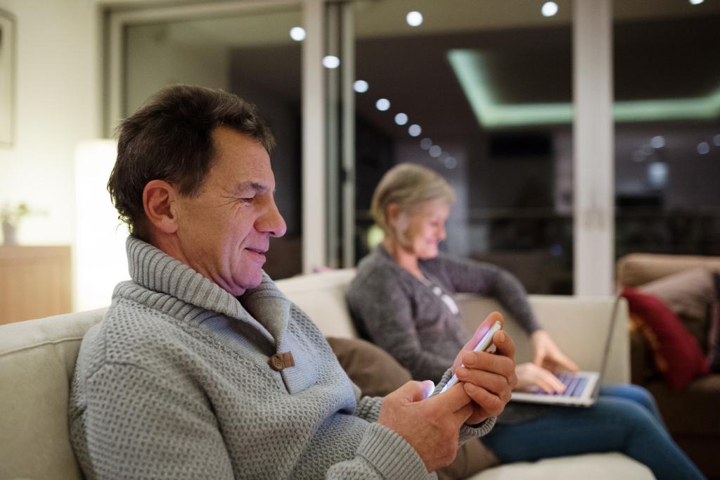 Älteres Ehepaar an Smartphone und Laptop auf dem Sofa