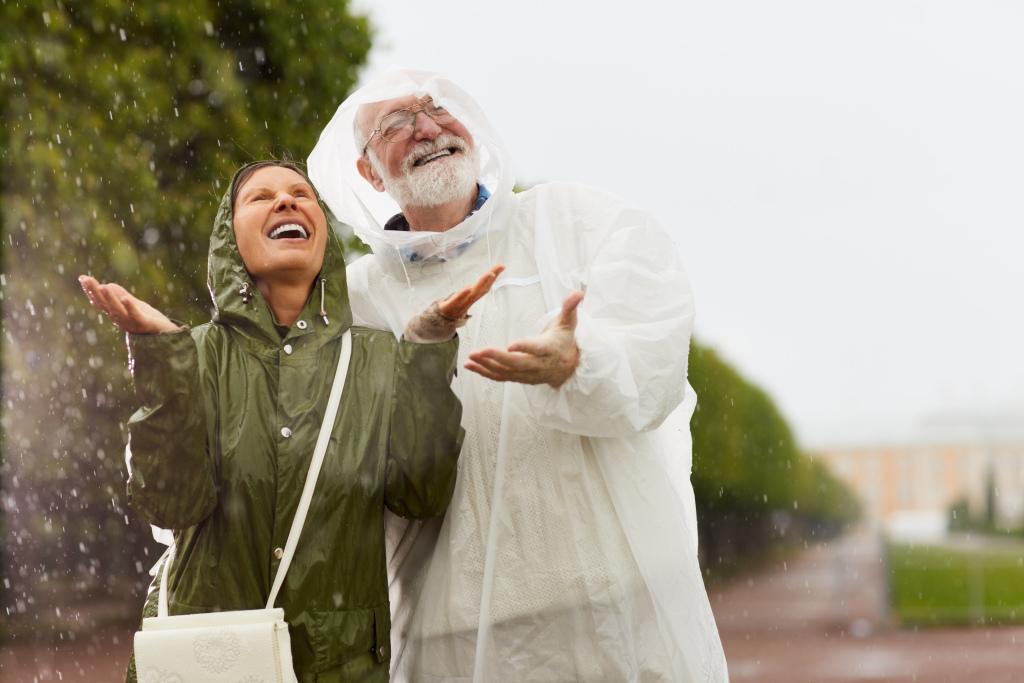 fröhliches Paar im Regen
