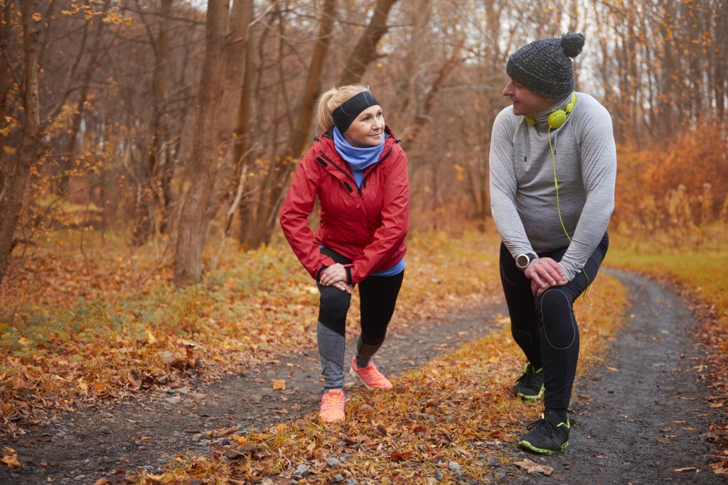 Eine Frau und ein Mann im herbstlichen Wald beim Sport