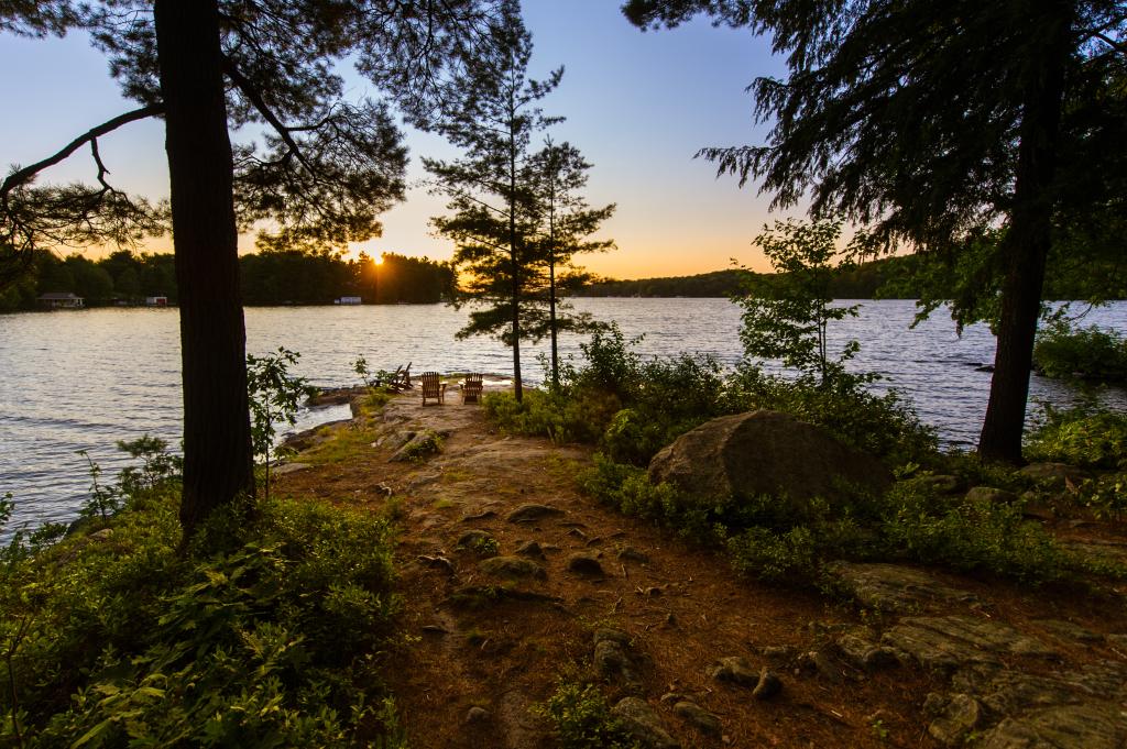 zwei leere Stühle an einem See im Wald