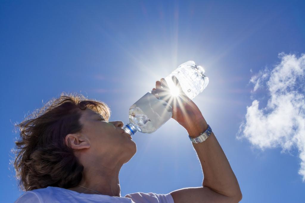 Eine Person trinkt Wasser in der Sonne