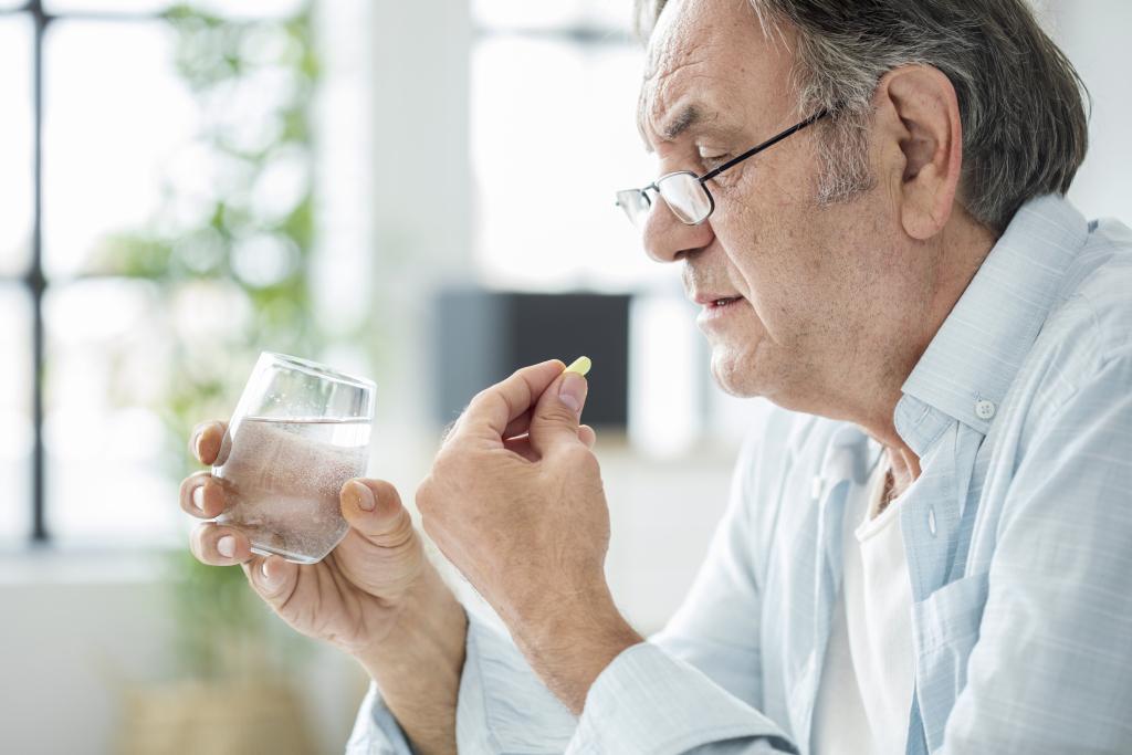Älterer Mann nimmt Medikament mit einem Glas Wasser ein