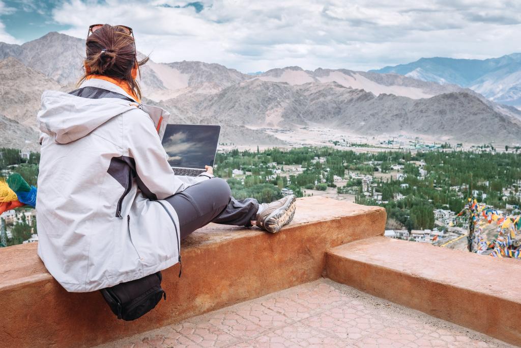 Frau mit Laptop mit guter Aussicht auf die Berge