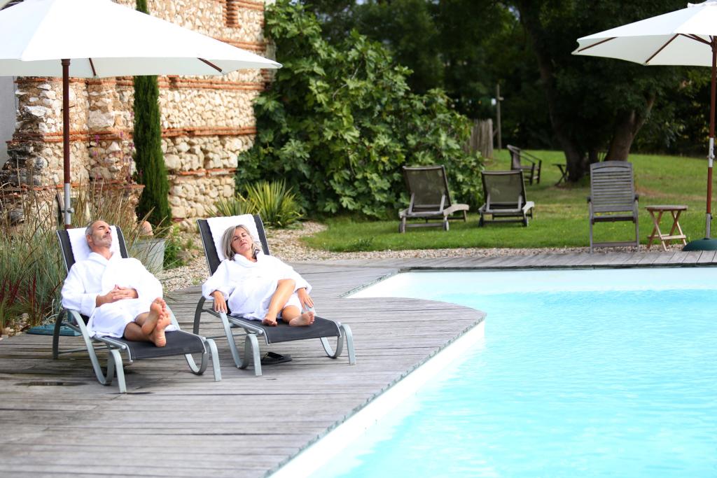 Ein Paar auf Liegestühlen am Pool