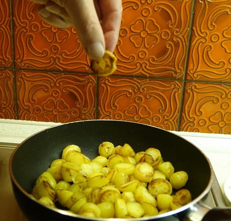 Hand, die eine Bratkartoffel stibitzt