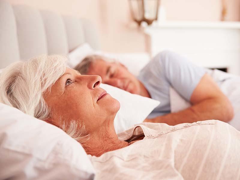 Ältere Dame, die schlaflos im Bett liegt