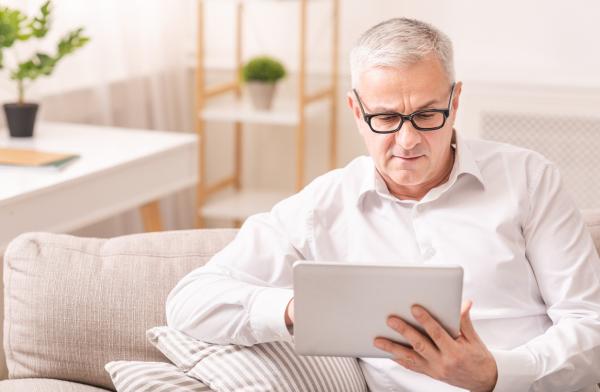 Älterer Mann schaut auf ein Tablet