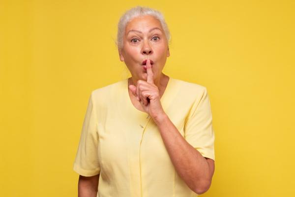 Ältere Dame, die sich den Finger auf die Lippen legt