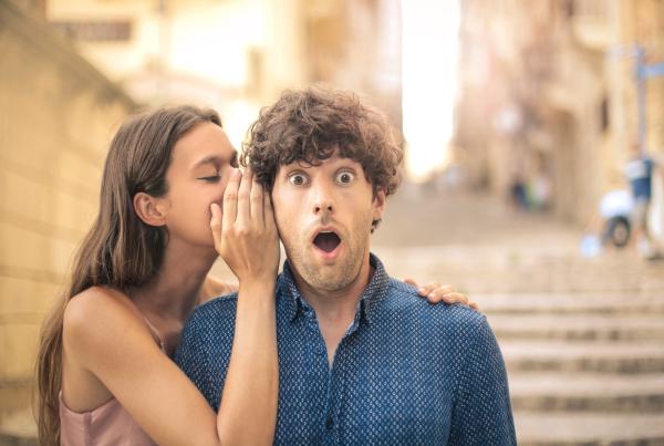 Mann, der mit aufgerissenem Mund ein Geheimnis erzählt bekommt