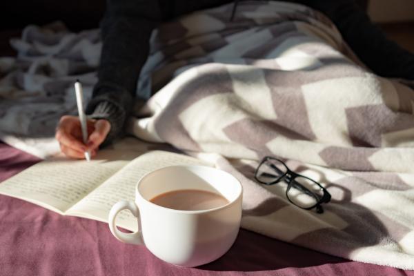Autorin auf Bett mit Kaffee, Stift und Papier