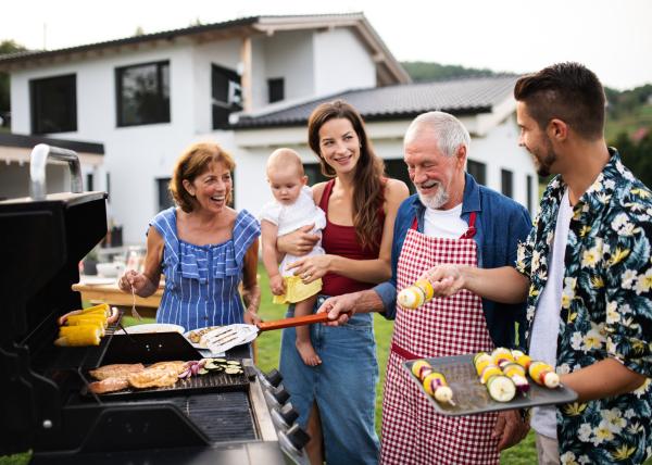 Mehrere Generationen beim Grillen im Garten