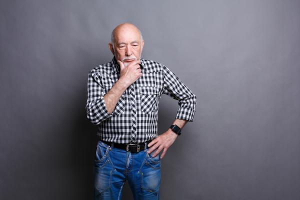 Älterer Mann, der grübelnd vor einer grauen Wand steht