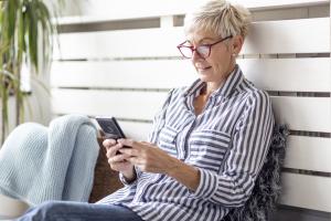 Seniorin schaut auf Smartphone-Screen