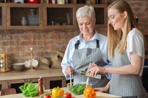 Eine jüngere und eine ältere Frau geben Öl zu einem Salat