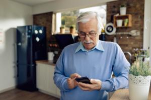 Mann mit Handy an Küchentheke gelehnt