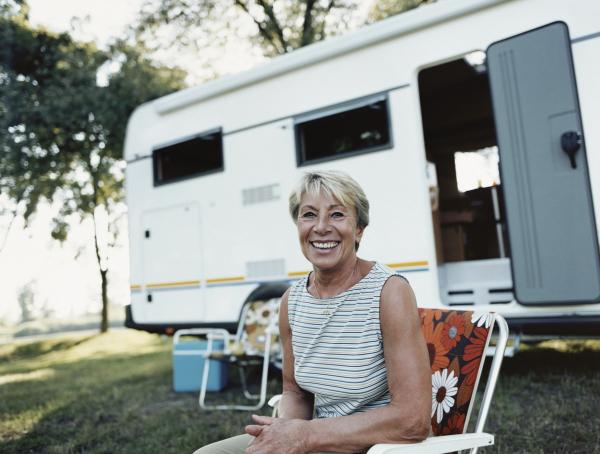 Seniorin mit Wohnmobil auf dem Campingplatz