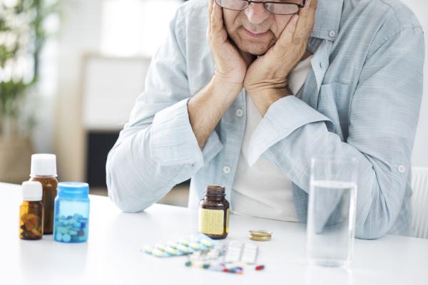Älterer Mann sitzt ratlos vor verschiedenen Medikamenten