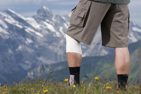 Wanderer mit bandagiertem Knie in den Bergen