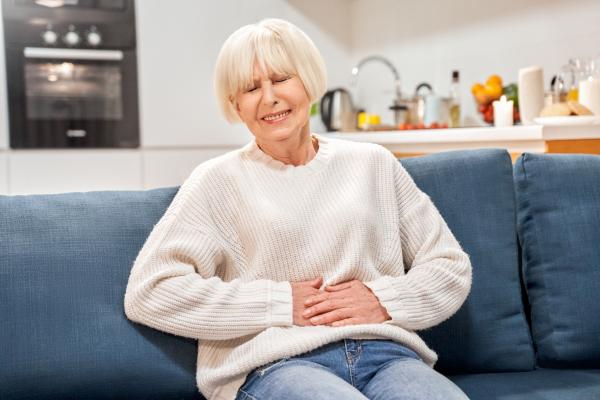 Ältere Frau, die sich den schmerzenden Bauch hält.