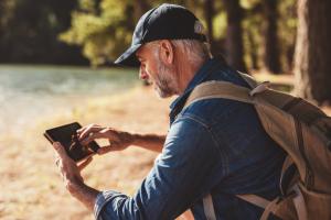 Senior mit Handy beim Wandern
