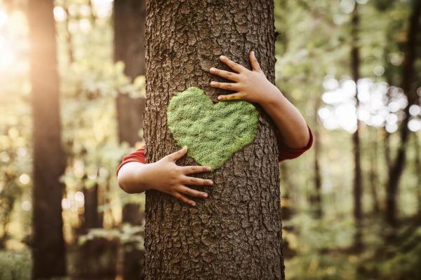 Kinderarme, die einen Baum mit einen Herz aus Moos umarmen