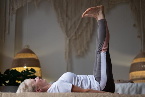 Seniorin auf dem Rücken liegend - die Beine nach oben gestreckt