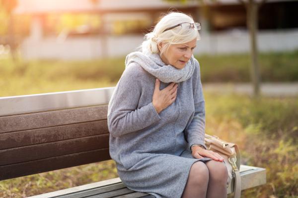 Ältere Frau, die sich mit schmerzverzerrtem Gesicht an die Brust greift