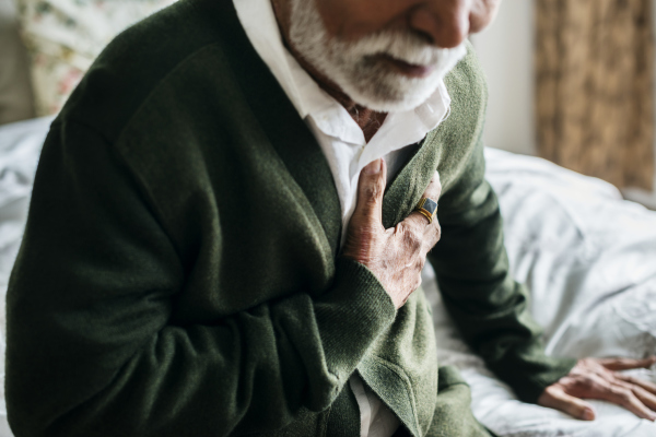 Älterer Mann, der sich an die Brust greift