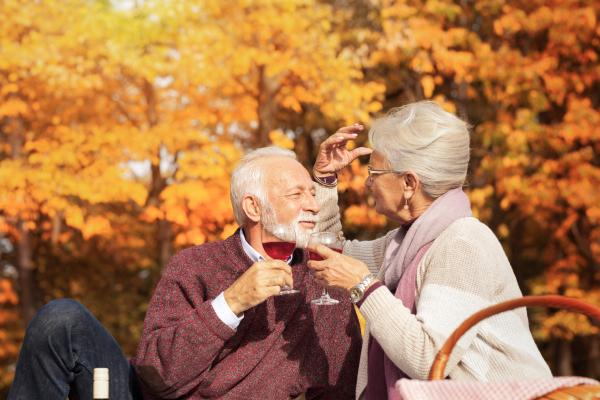Älteres Paar, das sich im Herbst draußen bei einem Glas Wein zuprostet