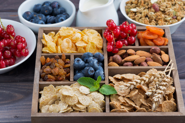 Frühstück mit Zerealien und anderen Zutaten in einer Holzkiste