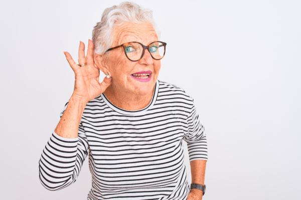 Ältere Dame, die eine Hand an ihr Ohr hält