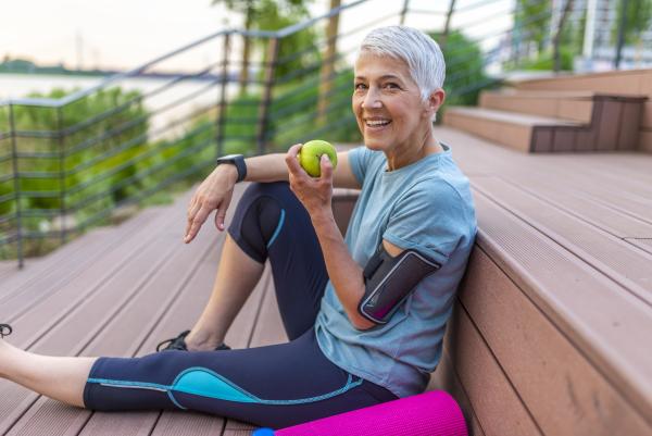 Sportliche ältere frau mit einem Apfel