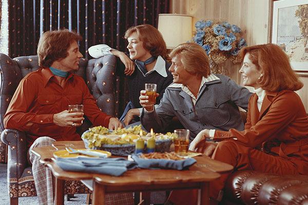 Zwei Paare um einen Tisch in den 1970er Jahren