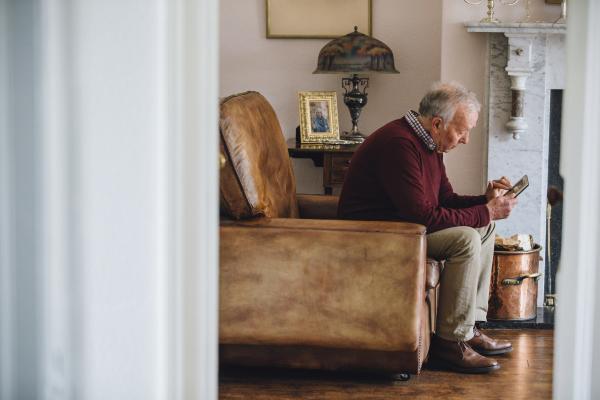 Trauriger Senior sitzt in einem Ledersessel