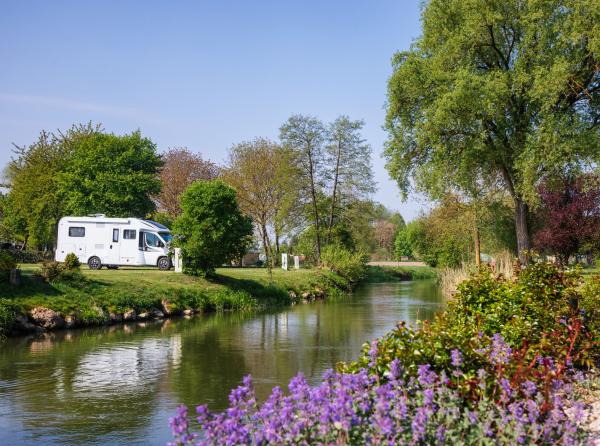 Wohnmobil auf einem Campingplatz an einem kleinen Fluss