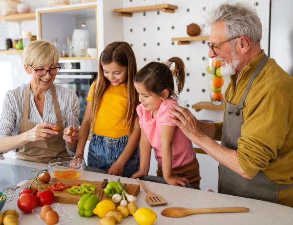 Großeltern kochen mit Enkelinnen