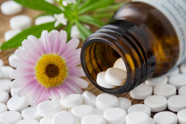Schüssler Salze mit Arzneimittelfläschen und Blume