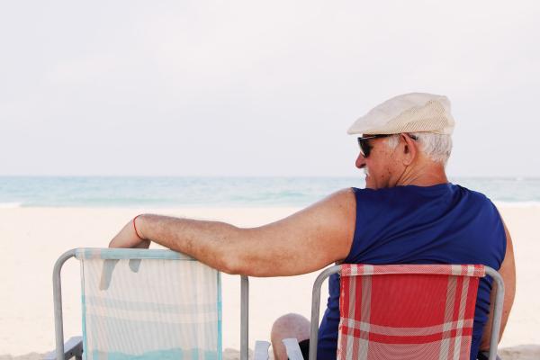 Einsamer Senior im Campingstuhl am Strand