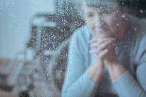 Frau schaut traurig aus verregnetem Fenster