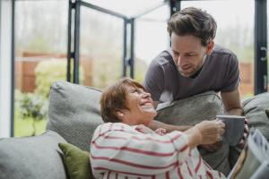 Eine Seniorin auf dem Sofa bekommt von einem Mann eine Tasse Tee gereicht