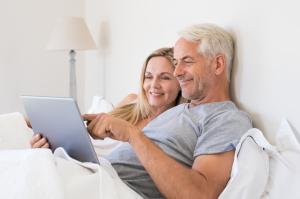 älteres Paar arbeitet im Bett an Tablet