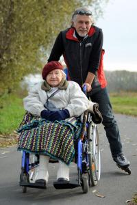Brigitte Schalk, Mann auf Inlinern schiebt Frau im Rollstuhl